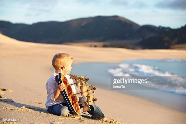 Kleiner Junge hält Boot am Strand bei Sonnenuntergang