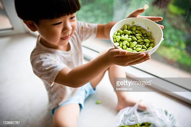 Little boy holding bowl of soybeans