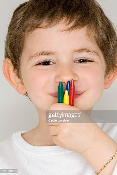 Little boy holding crayons