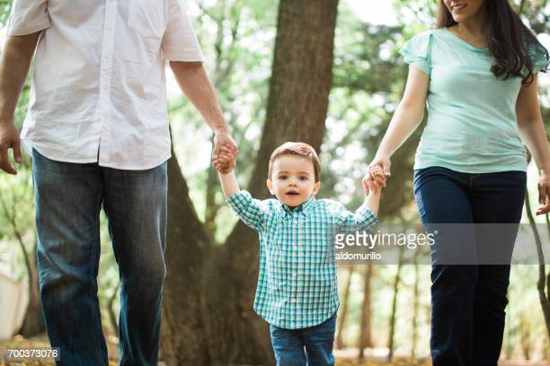 Little boy holding hands with parents and looking at camera