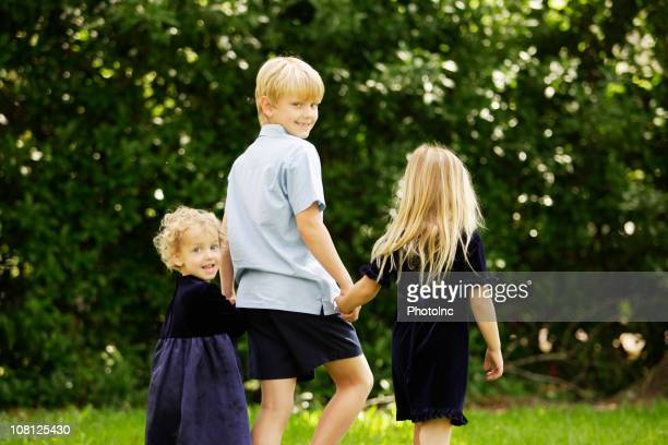 Little Boy Holding Hands with Sisters