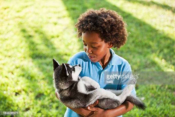 Little boy holding husky puppy