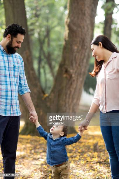Little boy holding parents and looking up