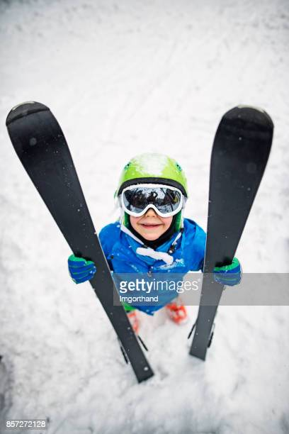 Little boy holding skis