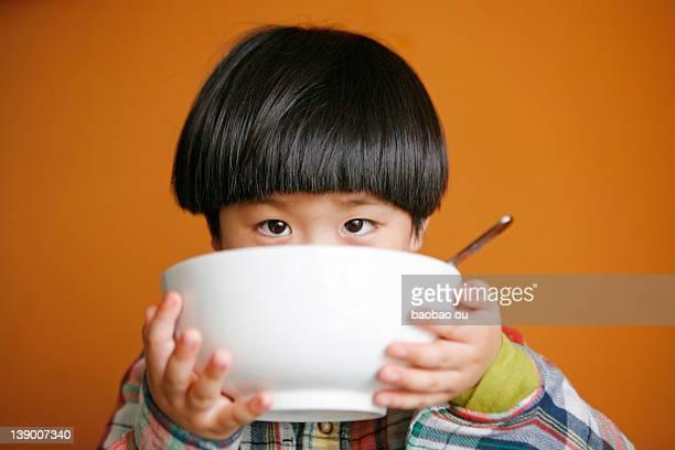 Little boy holding soup bowl
