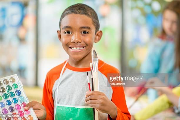 Little Boy Holding Up His Paint Colors