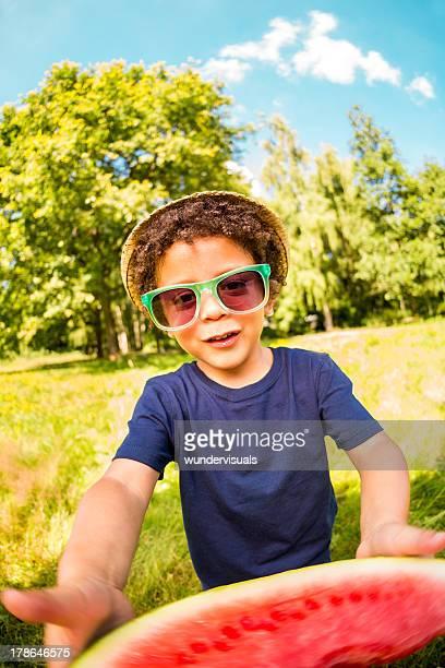 Little boy holding watermelon into camera