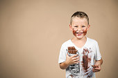 Little boy holds a bar of chocolate in his grin and has smudged clothes, against colored background