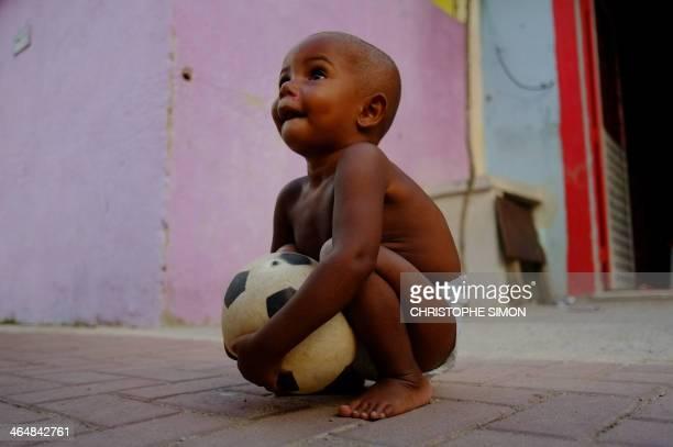 A little boy holds a football at the Cidade de Deus shantytown in Rio de Janeiro on January 23 2014 AFP PHOTO / Christophe Simon