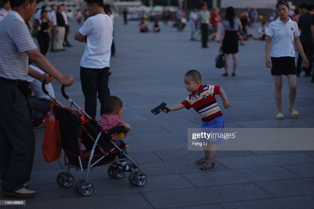 A little boy holds a toy gun at a passing child before the customary ceremony of lowering flag at Tiananmen Square on May 30, 2012 in Beijing, China.