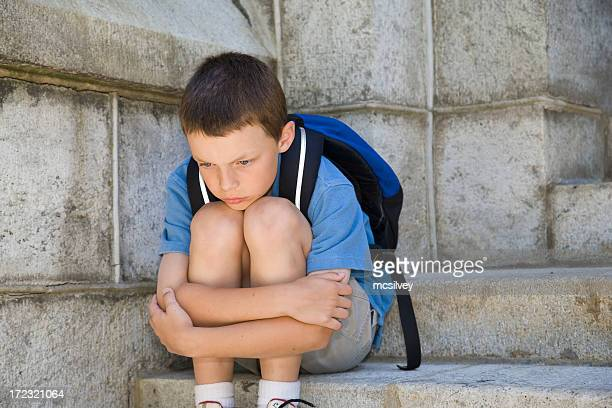 Little boy hugging his knees in desperation