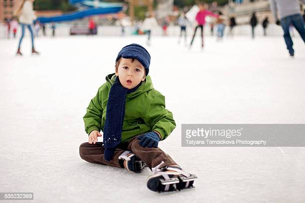 Little boy ice-skating in outdoor rink