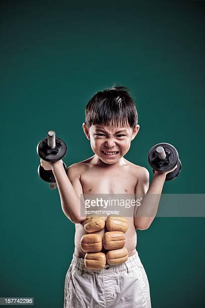 Petit garçon imagine qu'il a pris de force musculaire.