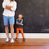 Indoor shot of little boy and his father standing with hands folded against black wall. Father and son looking at each other with copy space. Son imitating his father's pose.