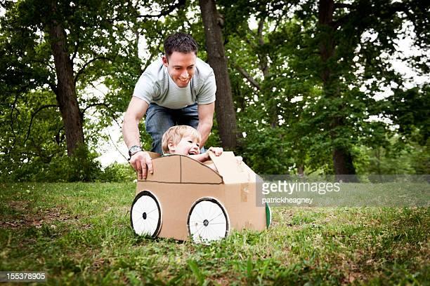 Kleine Junge in einem Karton Auto