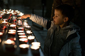 Little boy praying at the sacred place with burning candles in a catholic church