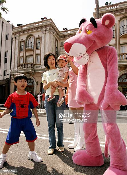 A little boy in a spiderman outfit checks out cartoon character the Pink Panther at the Universal Studios Japan in Osaka 13 July 2005 as the Pink...