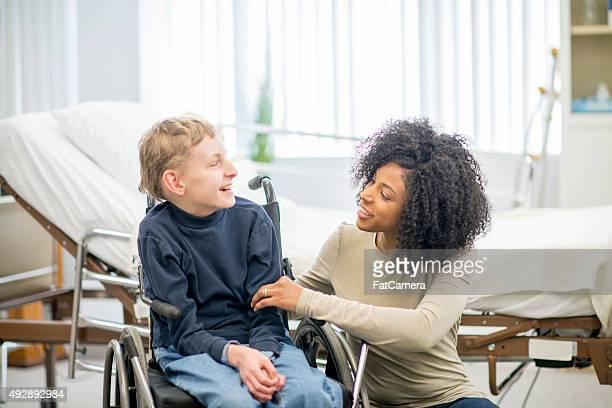Kleiner Junge im Rollstuhl mit seinem fürsorgliche