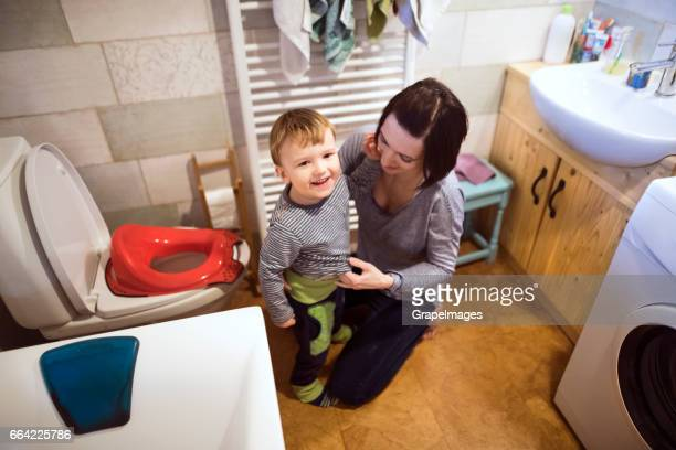 Little boy in bathroom next to the toilet, beautiful mother dressing him