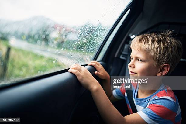 Little boy in car on rainy day