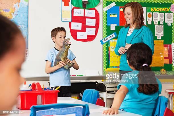 Kleine Junge in Klasse mit Dinasaur zu zeigen und sagen