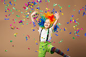 Little boy in clown wig jumping and having fun celebrating birthday. Portrait of a child throws up a multi-colored tinsel and confetti. Birthday boy. Positive emotions.
