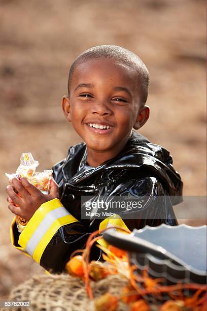 Little boy in firefighter costume smiling.