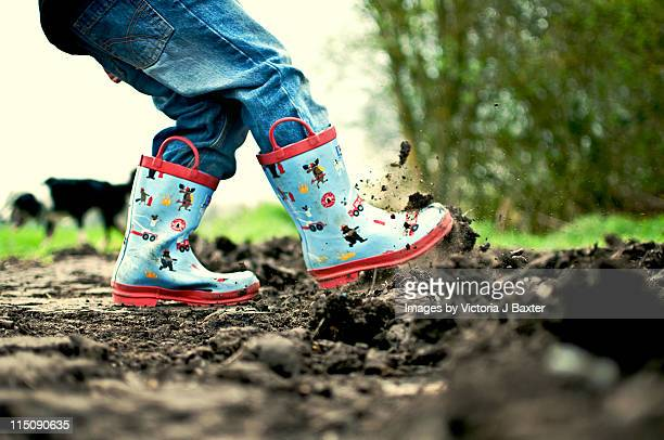 Little boy in his wellingtons kicking up dirt