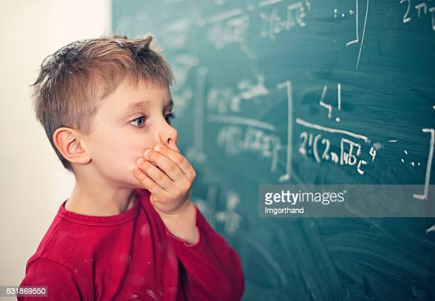Little boy in math class overwhelmed by the math formula