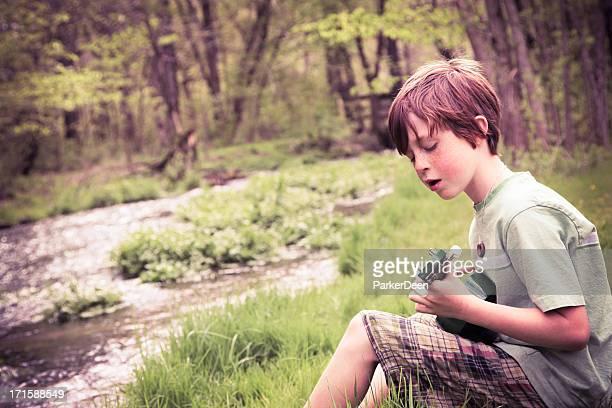 Little Boy in Nature Holding Ukulele