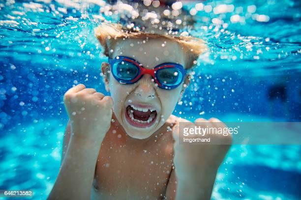 Kleine jongen in zwembad onderwater schreeuwen