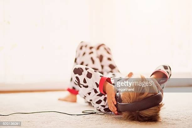 Little boy in pyjamas listening to the music in headphones