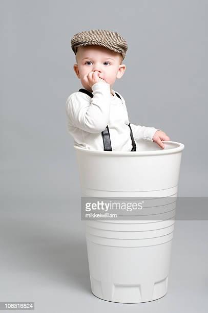 Kleine Junge im retro-Stil Kleidung steht im riesigen Papier Tasse