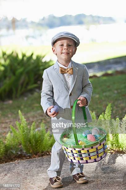 Kleiner Junge im Anzug hält Osterkorb