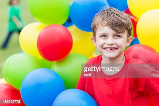 Little boy in the middle of big bunch of balloons