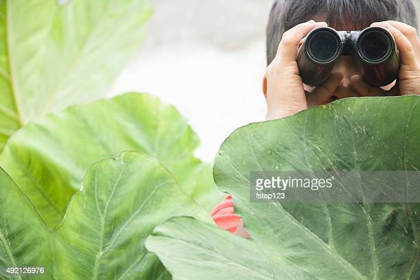 Little boy in tropical climate explores outdoors using binoculars.