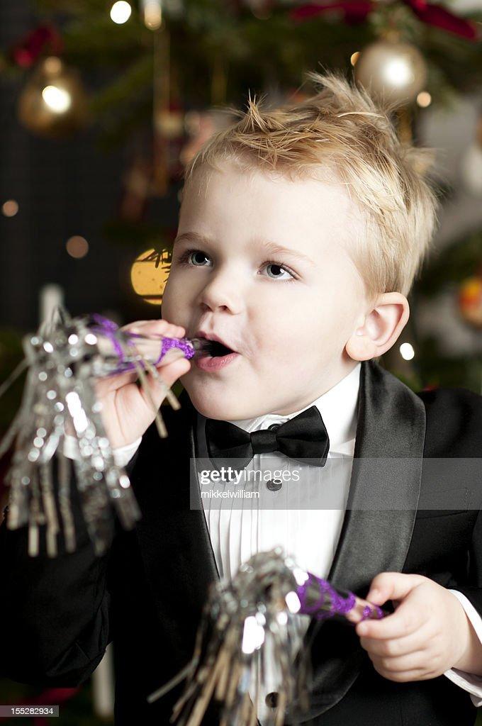 Little boy in tuxedo holds a party