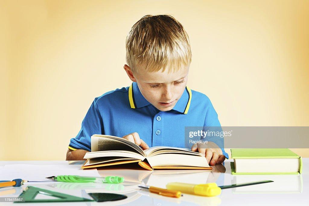 Little boy intent on reading book at school desk