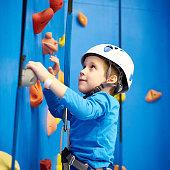 Little boy is climbing to amusement park on blue wall