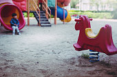 little boy is playing lonely in playground. little boy is sitting unhappy in playground.