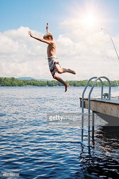 Little boy jumping in lake from pier on sunny day.