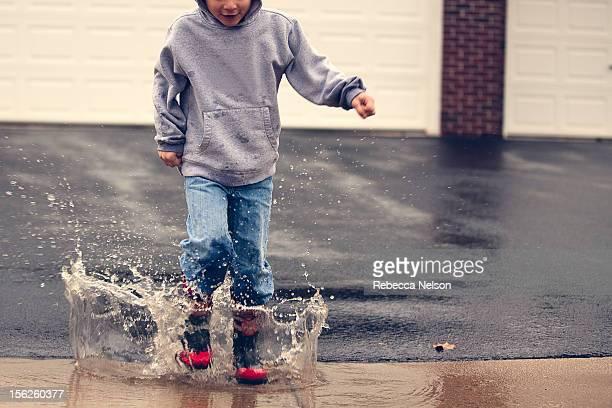 Little boy jumping in rain puddle