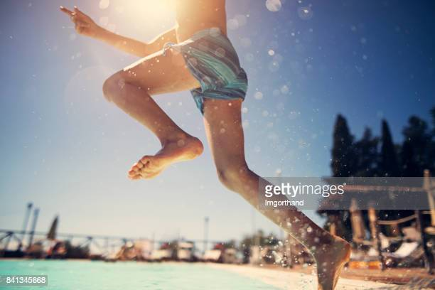 Little boy jumping into swimming pool