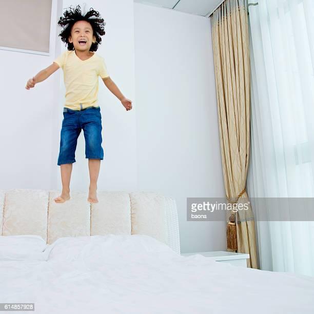 Poco niño saltar en la cama