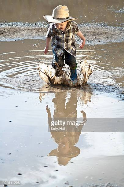 Little boy jumping through mud puddle