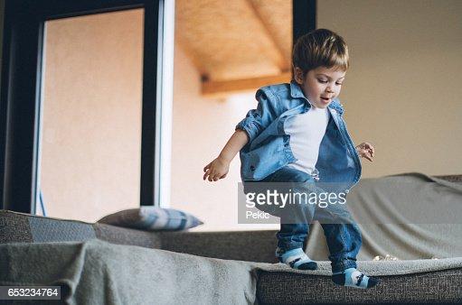 Little boy jumping with joy on sofa : Bildbanksbilder