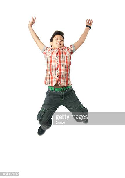 A little boy jumps for joy on a white background