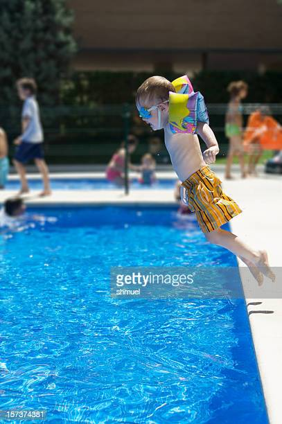 Little Boy Jumps Into a Clear Blue Pool