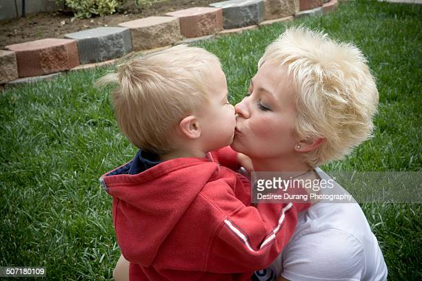 Little boy kisses mom on the grass lawn