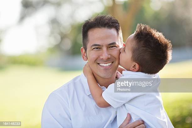Little Boy Kissing Father At Park